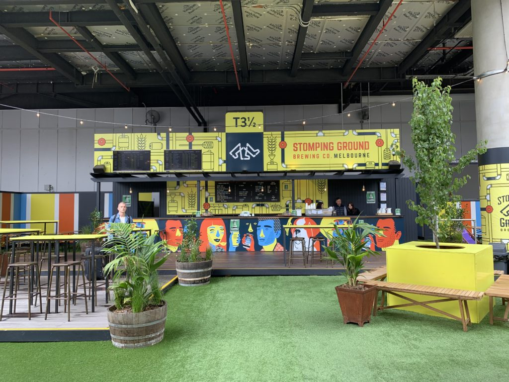 """A beer-drinking space with fake green carpet, plants and an outdoor """"atmosphere"""""""