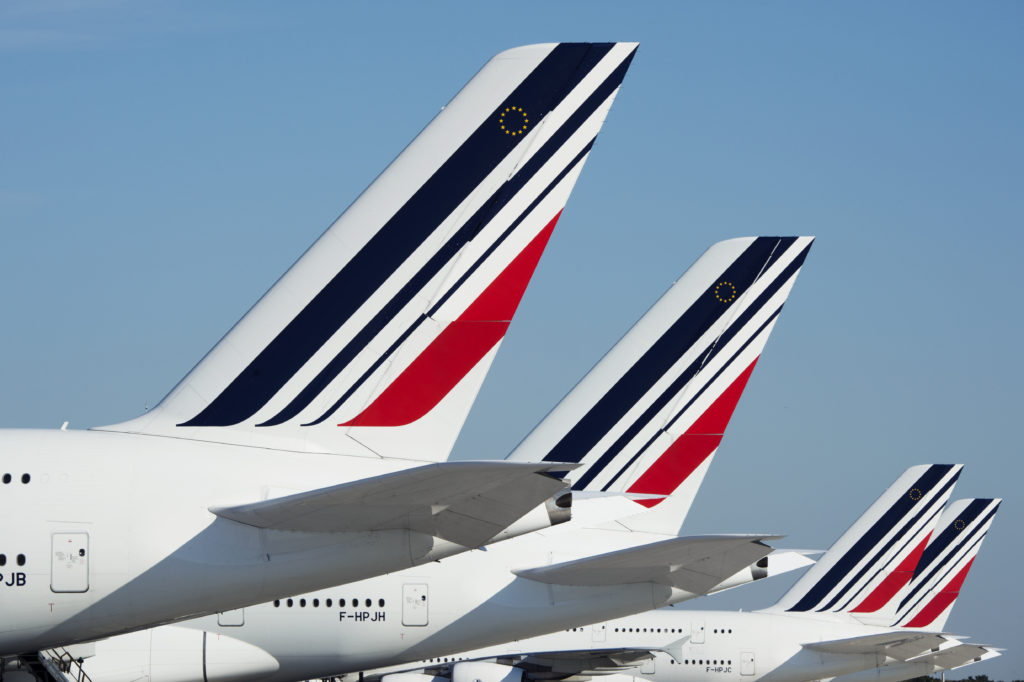 A series of parked A380 tails; the Air France colors are on display with a blue sky in the background
