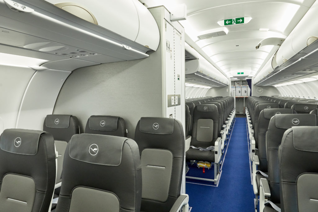 Rows of slimline seats and a lav on board an Airbus A321 operated by Lufthansa