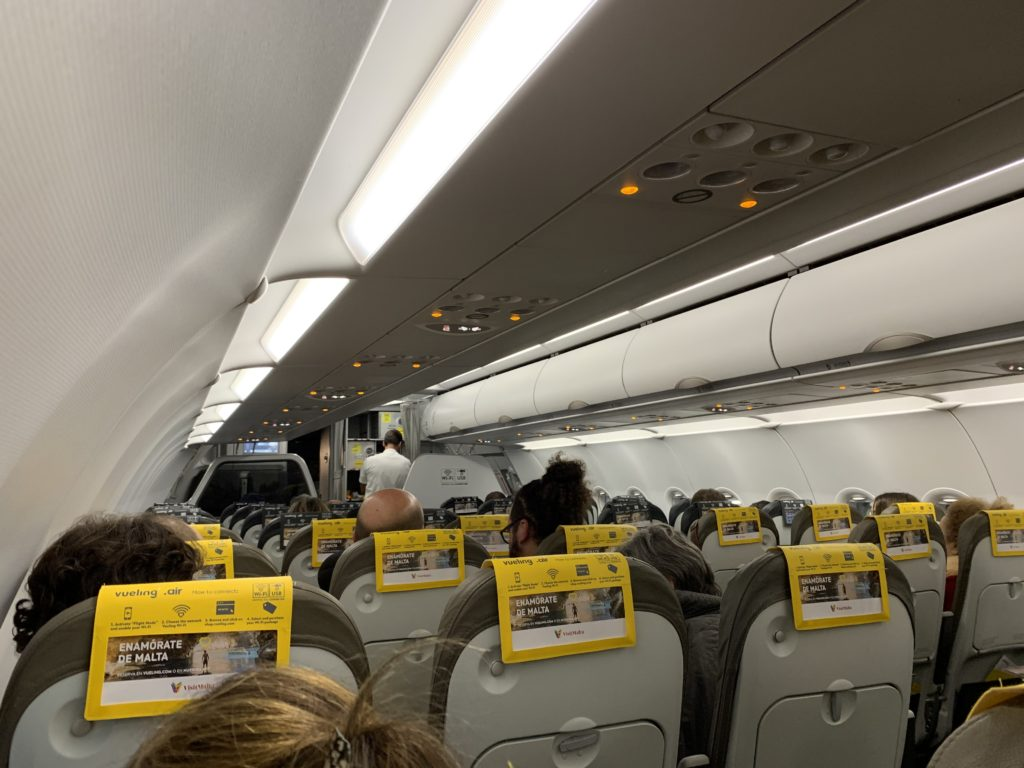 The Vueling cabin is very plain, with slimline seats and yellow headrest covers. this image shows rows of seats, and the backs of the heads of passengers