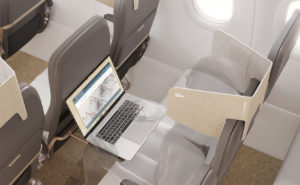 Slimline seats on board an aircraft. A laptop is seen on the tray table, and the HeadZone cardboard product is fixed to the top of the seat, providing privacy for the head.