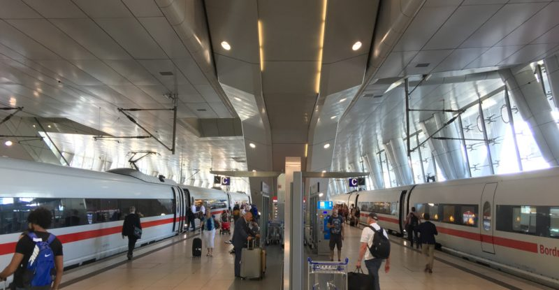 Frankfurt airport has a high-speed train station. Two trains are pictured at the station, green intermodality