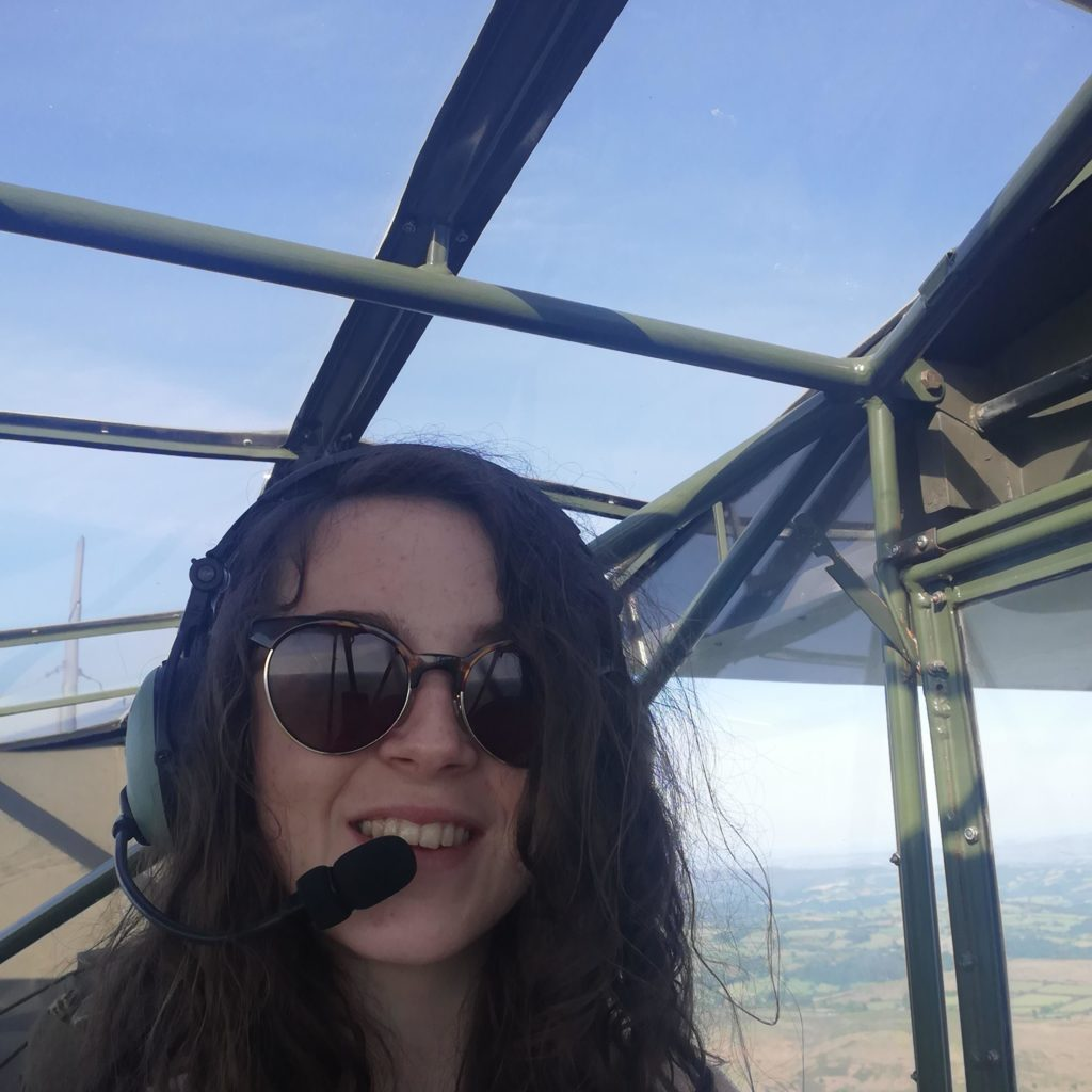 Ellie Carter piloting the airborne Piper Cub