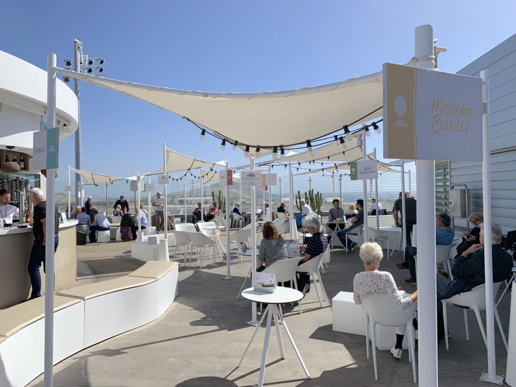 A beautifully sunny open space with a bar, tables, and white canopies in view. Passengers are enjoying the experience, and white and cream accents (chairs, tables, bar, canopies) complete the scene