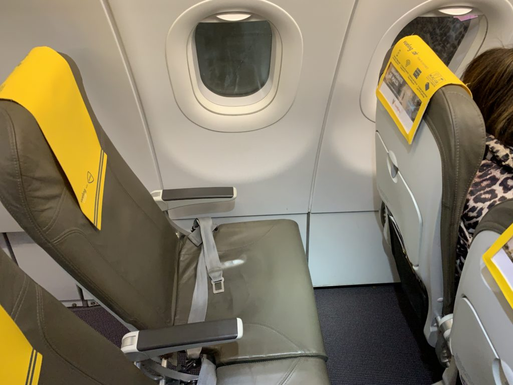 A Vueling slimline window seat with a yellow headrest cover