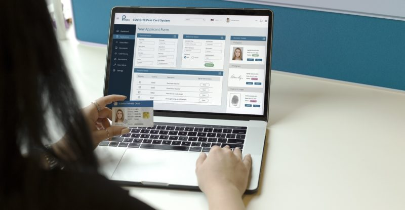 Pangea's Covid-19 Pass Card is shown, being held by a woman using a laptop to check her health data