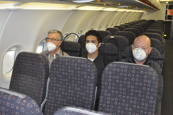 Three men, wearing masks, are seated in a narrowbody aircraft. The image shows the PPW on either side of the middle seat, which protects all passengers