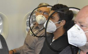 Three men, all wearing masks, seated on board a narrowbody with protective shields at their seats. The shields are on either side of the middle seat, offering protection to all three passengers