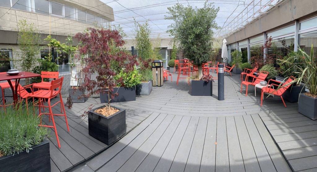 Orange-pink high top tables and chairs, plus regular chairs are seen in the sunshine with a variety of plants.