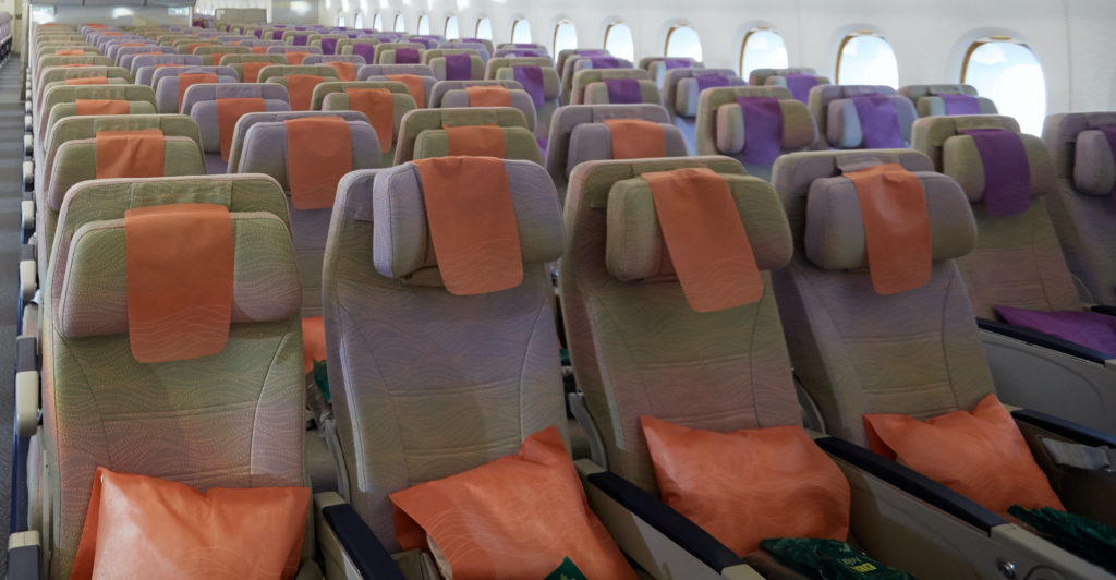 Rows of seats with orange pillows and orange headrest covers on a widebody