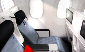 An Air France premium economy seat in blue and navy, with a red pillow.