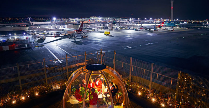Virgin Atlantic open air space atop a terminal, at night. Travelers are sharing a meal, with many aircraft in the background
