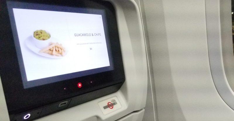 A seatback IFE screen showing onboard menu items