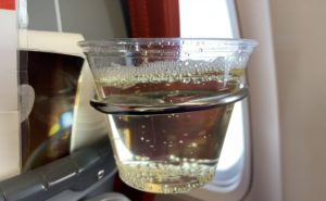 A glass of bubbly in a plastic cup, positioned on a seatback cup holder in-flight