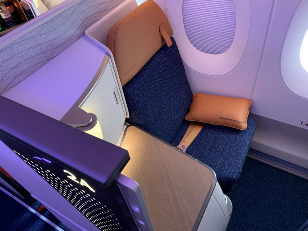 Aeroflot's new business class seat is nicely enclosed. The headrest and pillow are colored burnt orange, and purple LED lighting adds to the calm effect