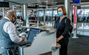 A passenger with a mask at the gate desk. A gate agent, also wearing a mask, looks at the passenger's mobile device