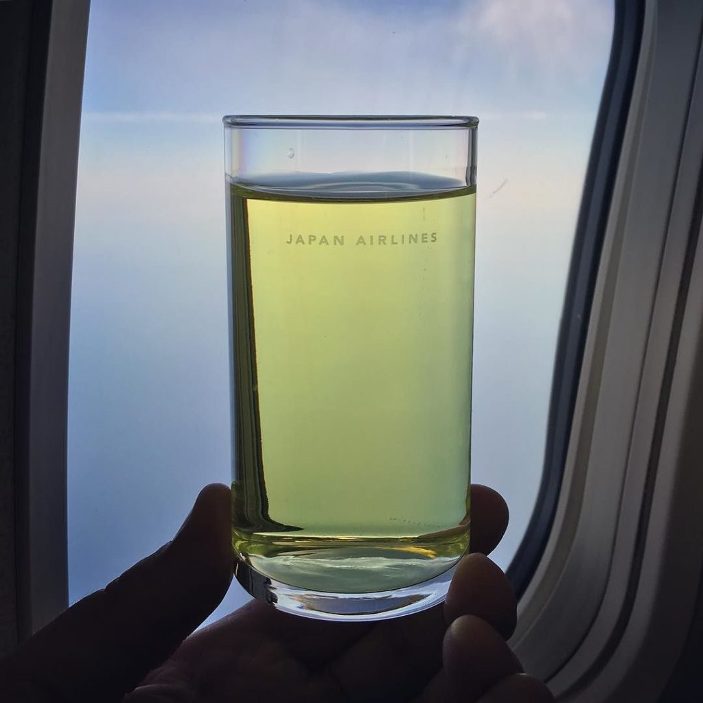 A glass with JAL's SKY TIME drink, being held up to the light of an aircraft window