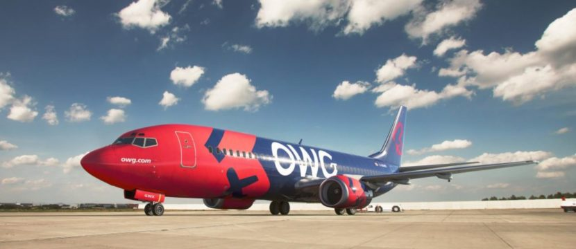The OWG 737-400 in navy and red livery parked, with a blue sky in the background with puffy white clouds