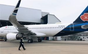 A Qingdao Airlines A320 parked outside a hangar, with a blue tail and red design