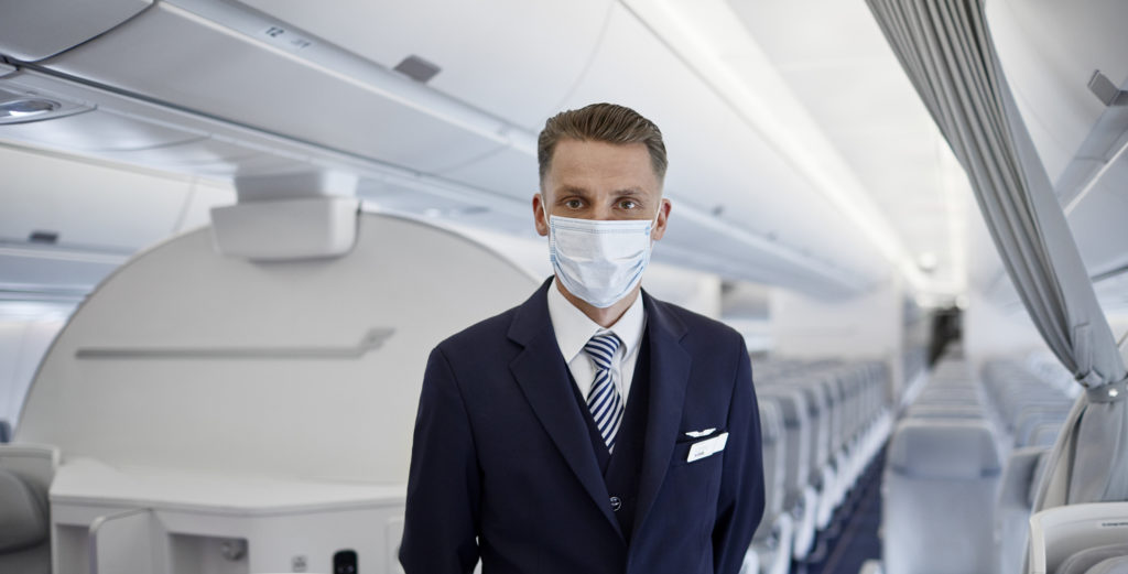 A masked male crew member on board a Finnair widebody