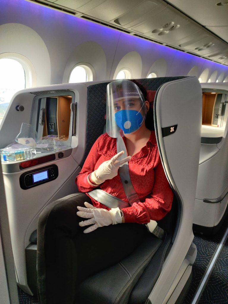 A business class passenger, in a Vistara business suite, giving the peace sign. She is wearing gloves, a mask and a visor