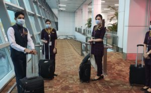 Vistara crew of four - two men and two women - in masks and uniforms, ready to board.
