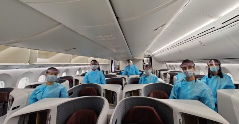 Vistara's crew, in full PPE, standing behind the business class seats aboard the carrier's new 787
