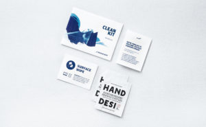 The contents of the kit, including hand sanitizer wipes, are laid out on a white background