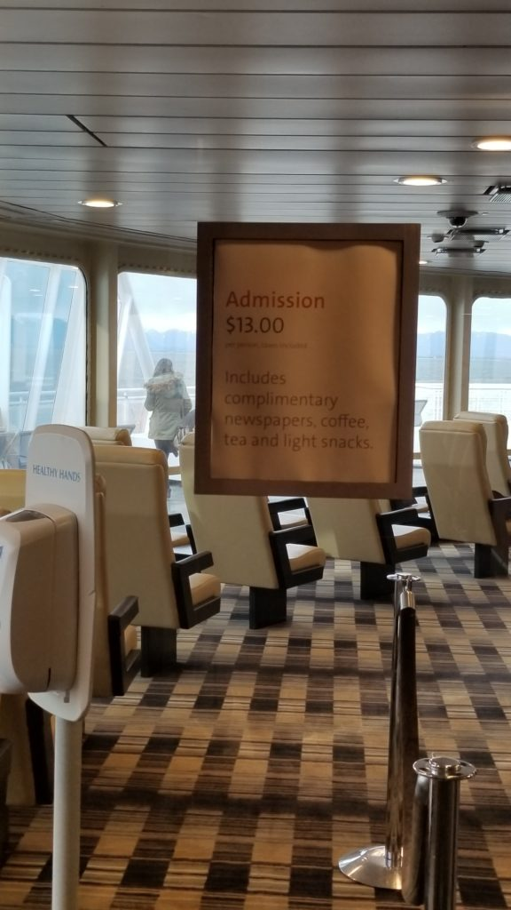 A sign stating that the lounge costs CAD$13 to enter. Comfortable cream chairs are in the background, and a plush carpe.