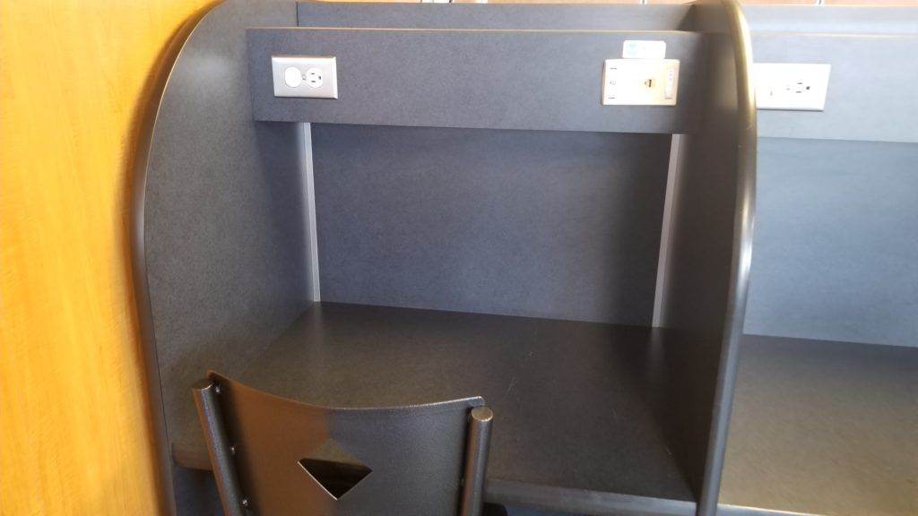 A cubicle with a desk, chair and power ports