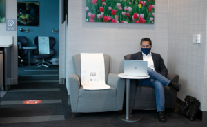 A passenger, wearing a mask and seated in a lounge. Beside him, a seat is blocked for social distancing