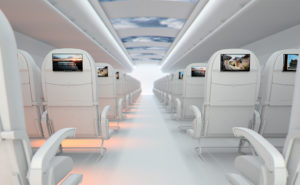 An image of an aircraft cabin, with white seats and seatback screens. A display on the ceiling shows clouds and blue sky inside the aircraft