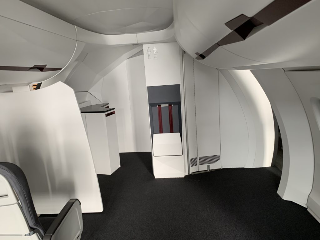 A touchless cabin interior concept shared by Diehl. This image shows the interior of an aircraft, with dark carpet and white surfaces