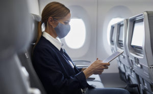 A female passenger in a mask, using her device on board a Finnair widebody
