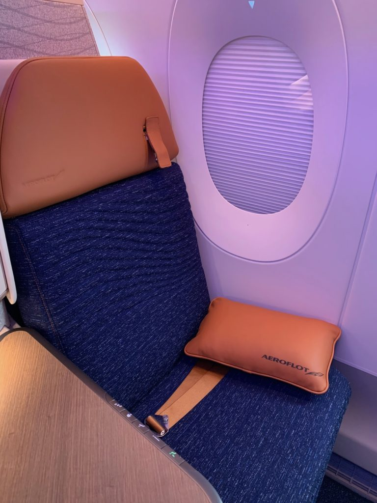 The Horizon Premier seat, upright and at the window, as seen on the Aeroflot A350. It features blue and burnt orange material. A purple LED light creates a calming mood by the seat