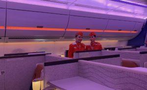 Two flight attendants stand beside the Horizon Premier suites aboard Aeroflot's A350