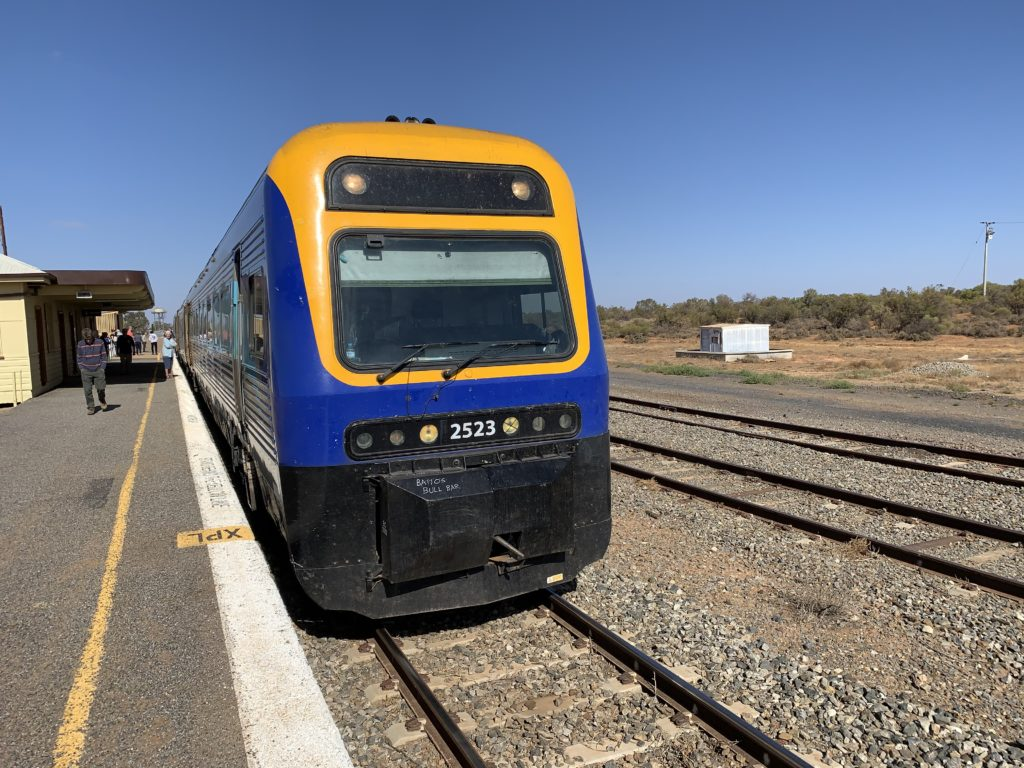 The Outback Xplorer train, in blue and yellow, on the tracks on a beautiful day with blue skies and no clouds