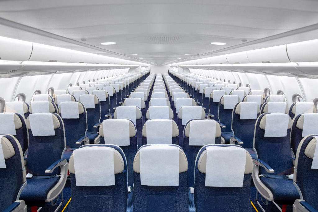 Rows of seats on a Hi Fly widebody. The seats are blue with white headrests and white headrest covers