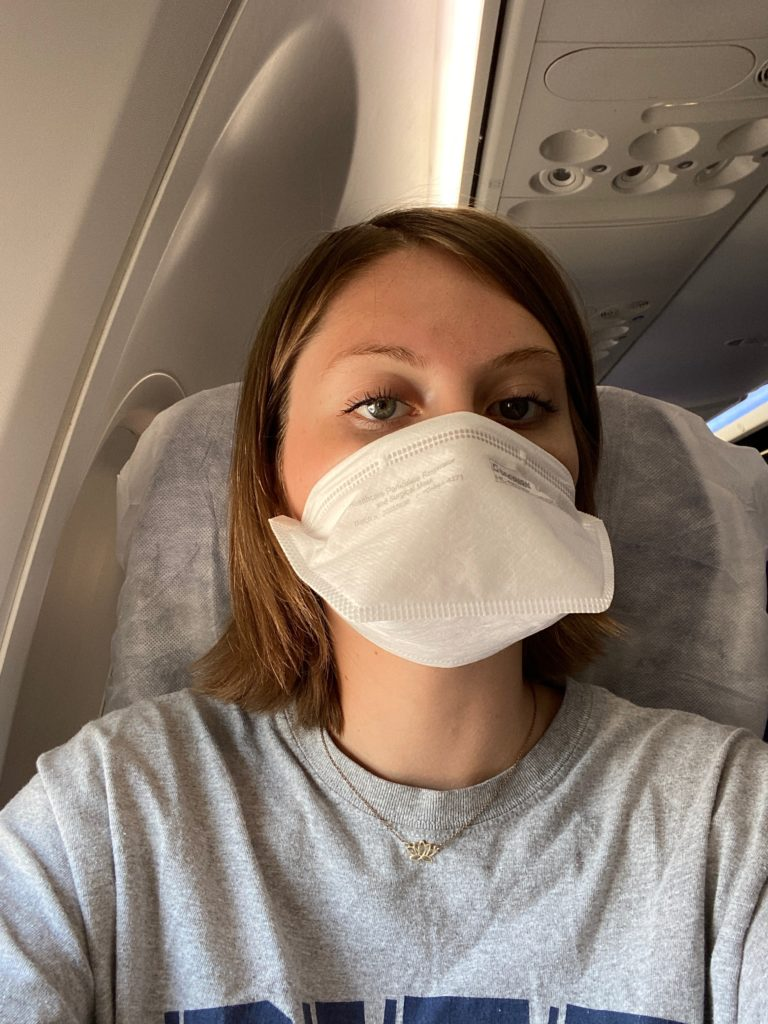 A photo of the author on board the Southwest 737. She is wearing a mask, and sitting on a seat cover from Seat Cuvers