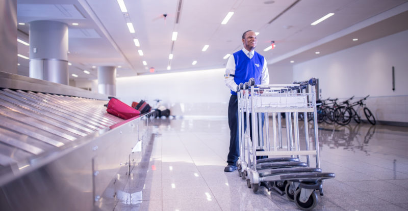 A man wheels sparkling clean luggage carts beside the baggage claim area in an airport