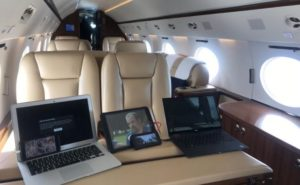 Three laptops, sitting on a table aboard a business jet