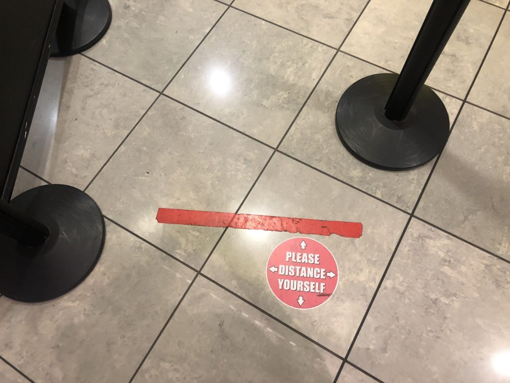"""A sticker on the ground at security, saying: """"Please distance yourself"""""""