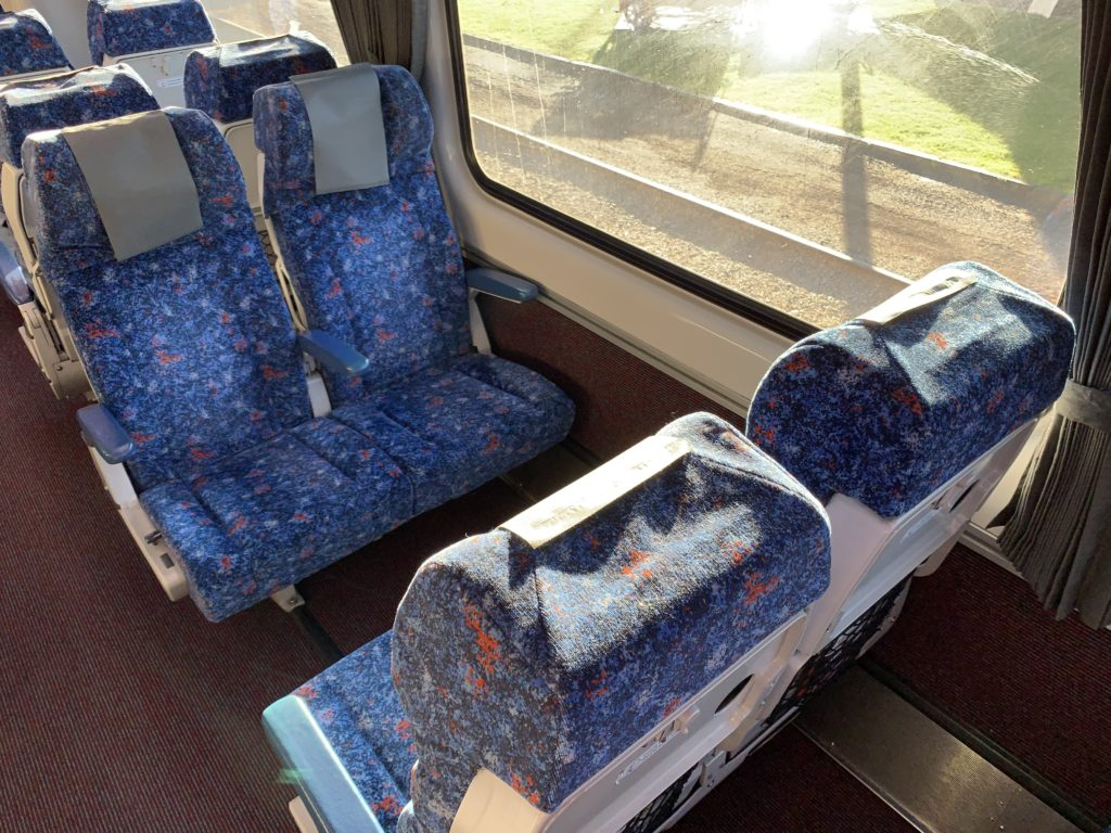 A seat quad on the train, with blue material. Two seats are facing another two seats