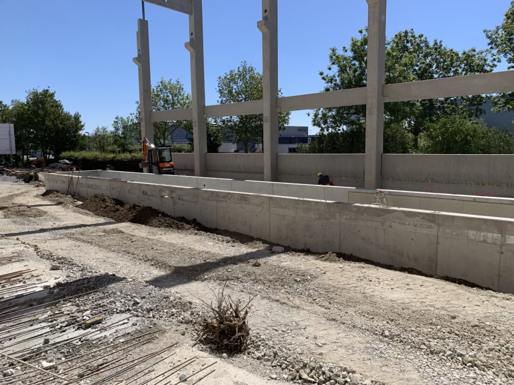 Under construction, the concrete foundational beginnings of Recaro's expansion plan are shown, with a blue sky and green trees in the background