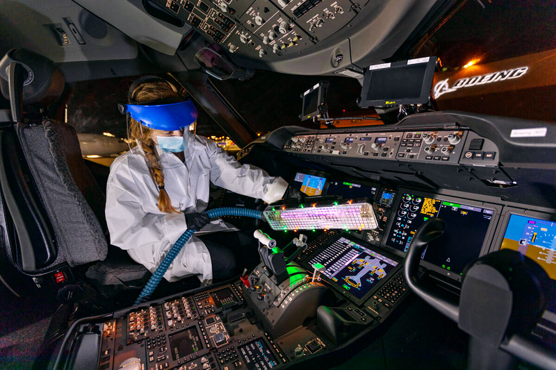 A woman wearing a mask, visor and other protective gear uses the mobile UV wand to disinfect the flight deck