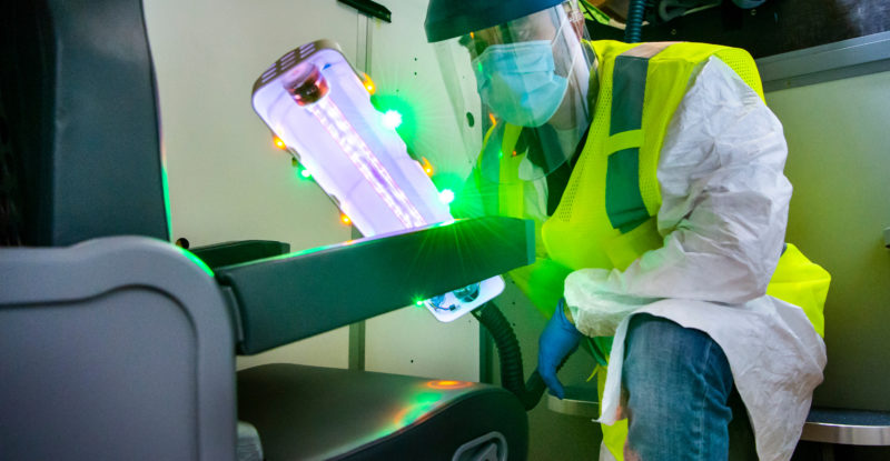 A man in a mask and other protective wear holds the mobile UV wand up to an aircraft seat to kill viruses
