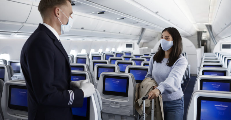 A male Finnair cabin crew member, dressed smartly and wearing a mask, communicates with a female passenger on board