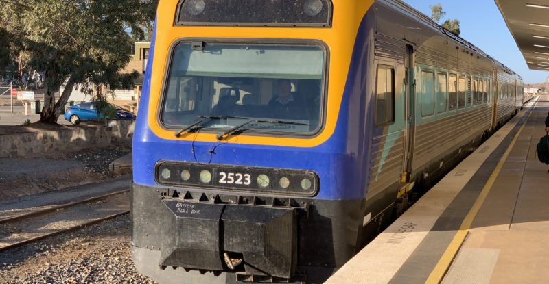 The Outback Xplorer train on the track, pained in blue and yellow
