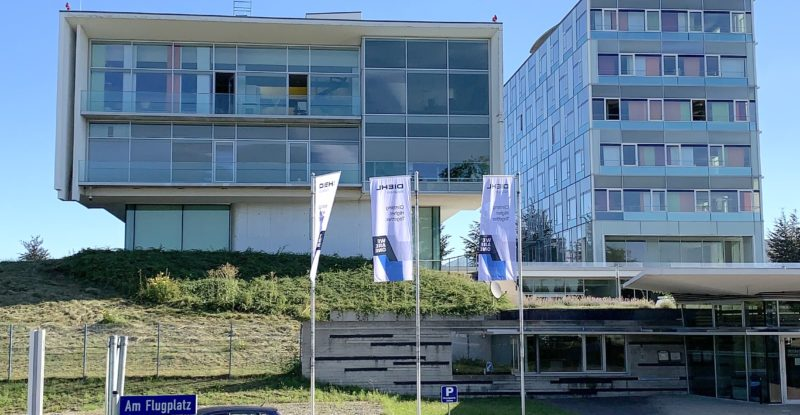 A picture of Diehl's offices in southern Germany. A blue sky serves as a backdrop to the building. Three flags are in front