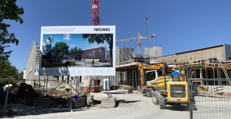 A large billboard with the name Recaro on it, and a blue sky as backdrop